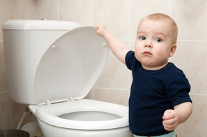 Child putting things in the toilet